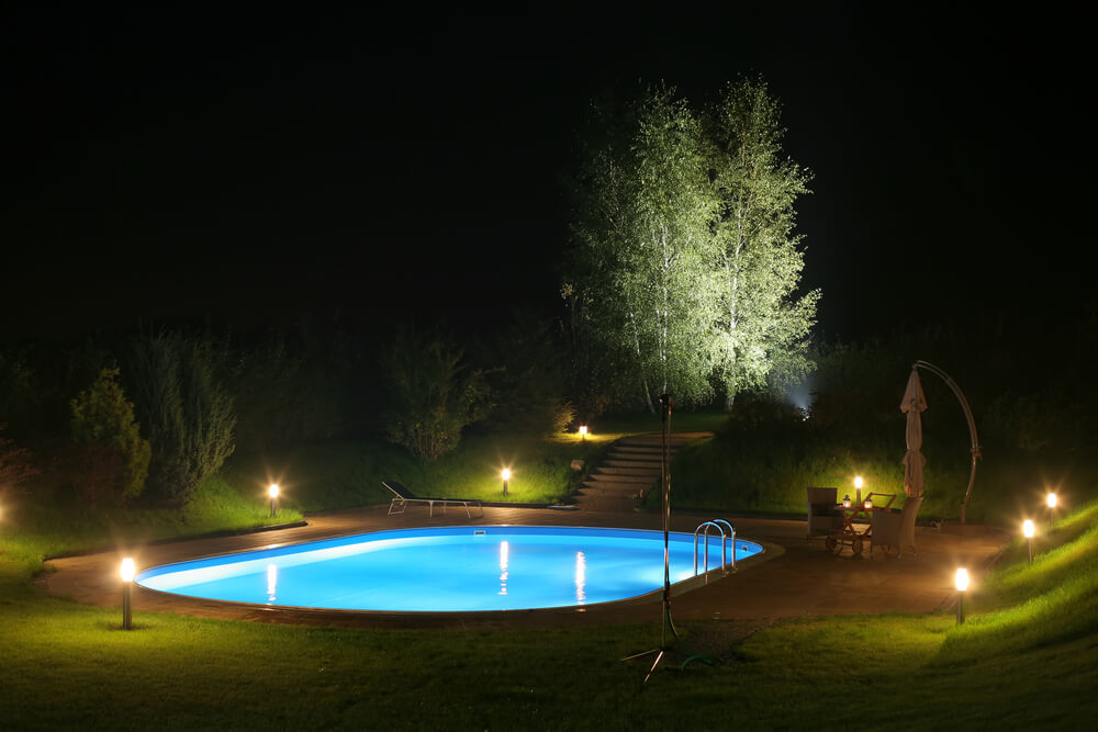 Backyard Pool At Night : Pool at night in lower level of the yard surrounded by lights, patio