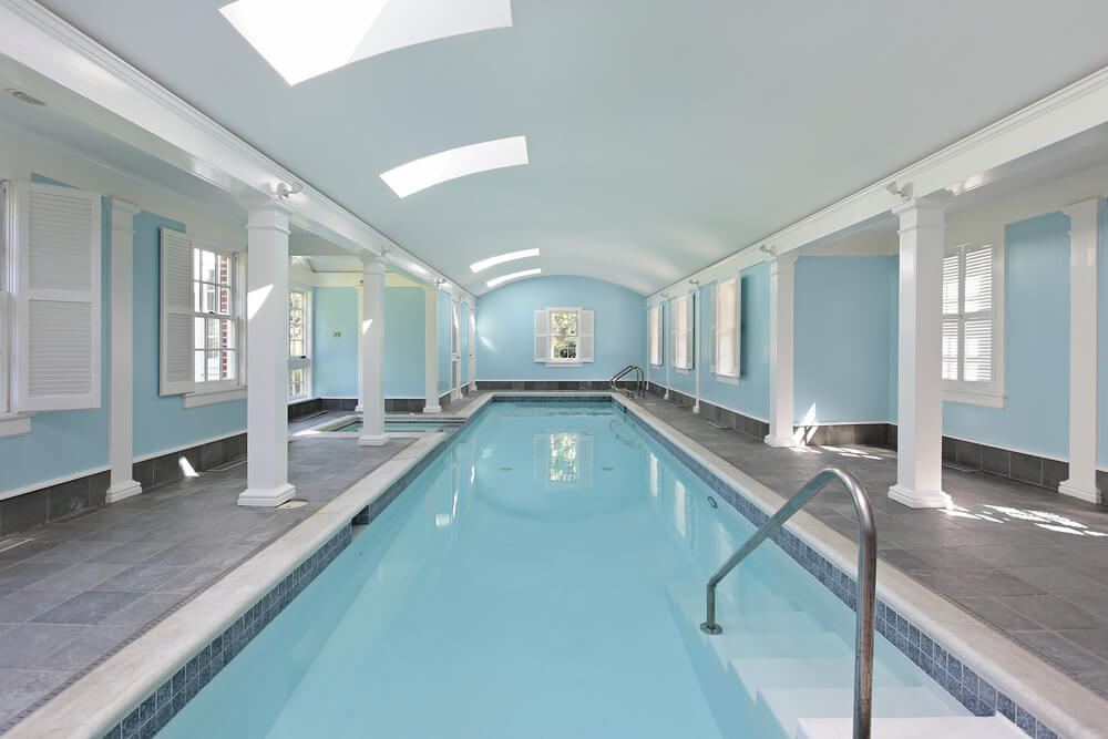 large indoor pool and hot tub in light blue walls and white support beams and white. beautiful ideas. Home Design Ideas