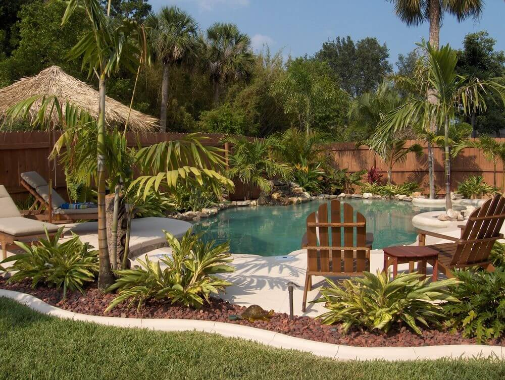 Tropical Backyard Pool With Rock Garden, Patio And Palm Trees.