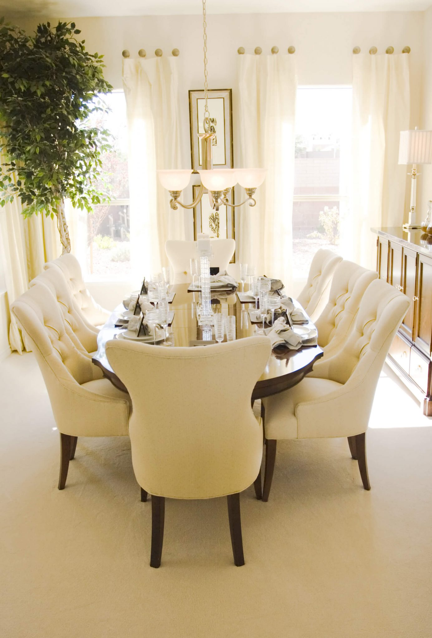 Wooden chairs for living room - Bright Sunny Dining Room With Oval Wood Table And Eight Plush Cream Colored Dining Chairs
