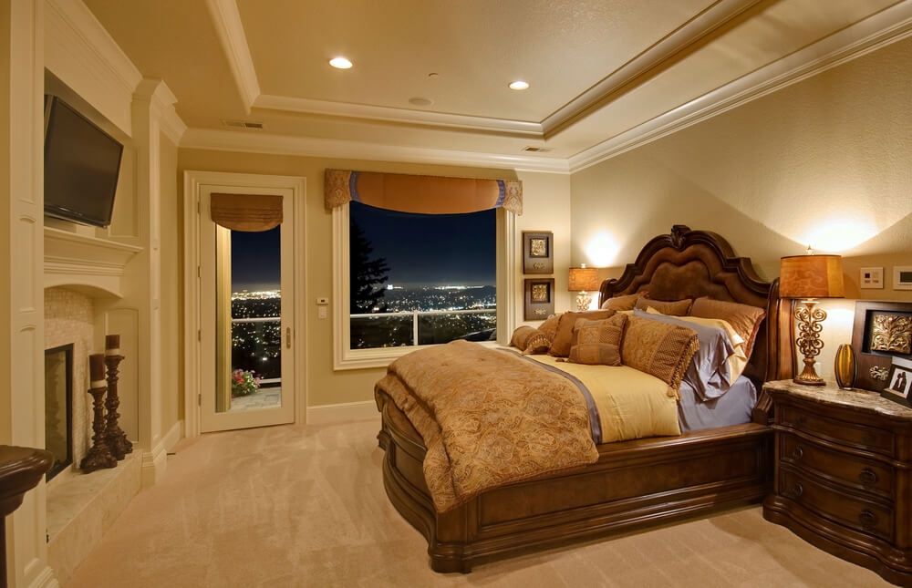 Luxury bedroom with fireplace, TV, balcony access with city views and large wood bedroom furniture.