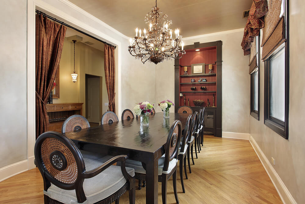 Formal Dining Room With Light Wood Floor Built In Shelving Chandelier Draped
