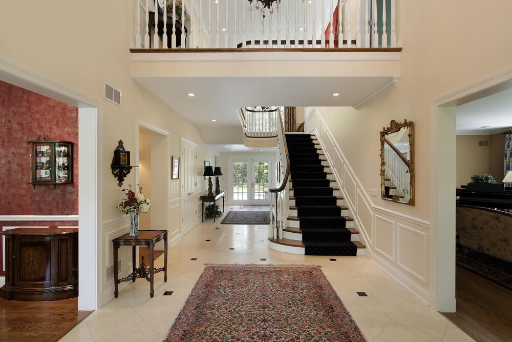 Entry hall with view of upper landing leading to straight staircase.  Foyer hall flows through the entire home to double glass doors leading out to the pool area in the backyard.