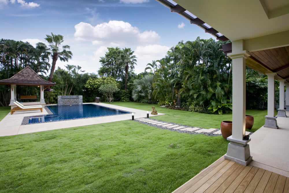 Tropical Home With Backyard Pool Surrounded By Small Patio, Grass And  Tropical Trees. One Part 79