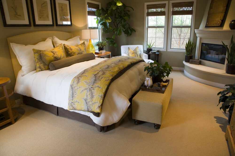 Master bedroom in beige color scheme with elevated gas fireplace in the corner.