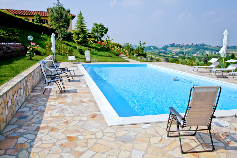 large rectangle pool with flagstone patio on sloped property overlooking valley and homes below
