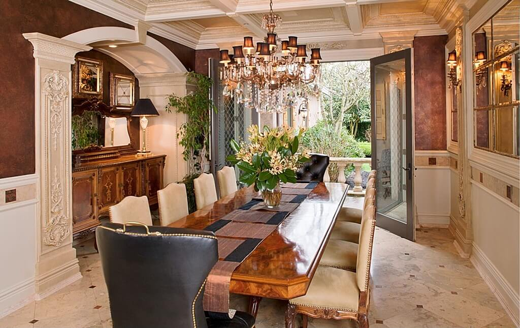 Ornate Dining Room With Double Doors That Open To A Patio And Backyard