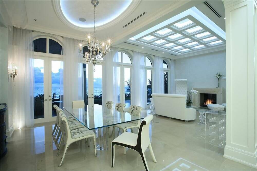 Modern all-white home with open living space containing large dining room  with glass table