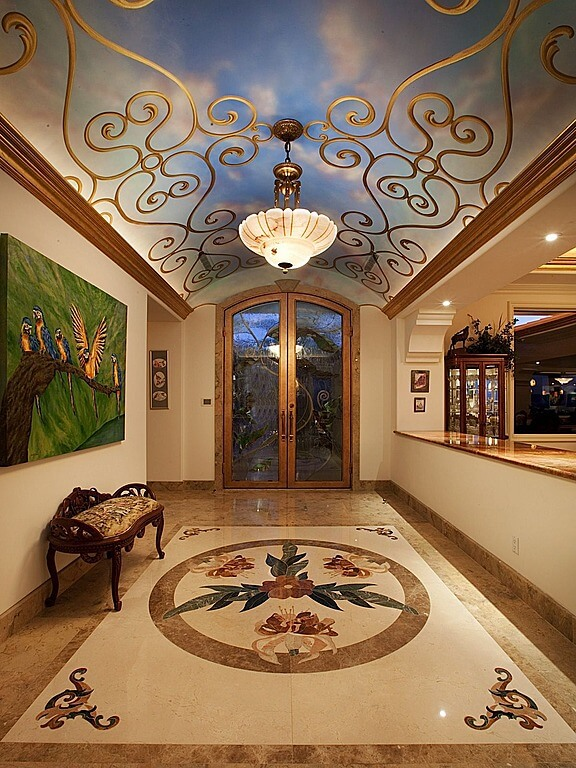 Entrance way with arched ceiling painted with a mural of the sky.