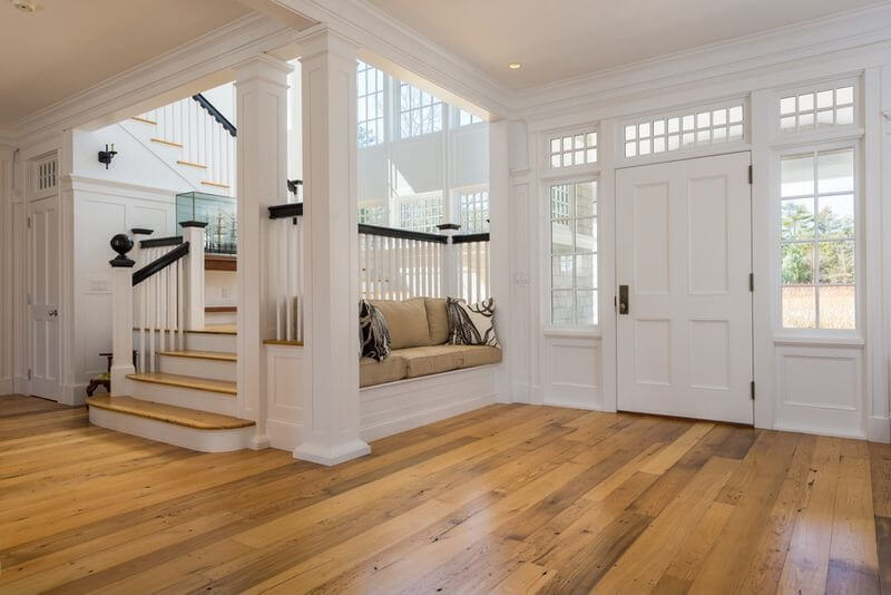 Simple yet elegant front entrance in white with wood flooring.  Small built-in sofa is to the right of the front door.  Stairwell is also to the right which is brightly illuminated with two stories of windows.