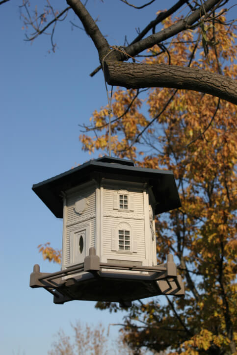 picture of an well crafted hexagon two story bird house replicating a home with front