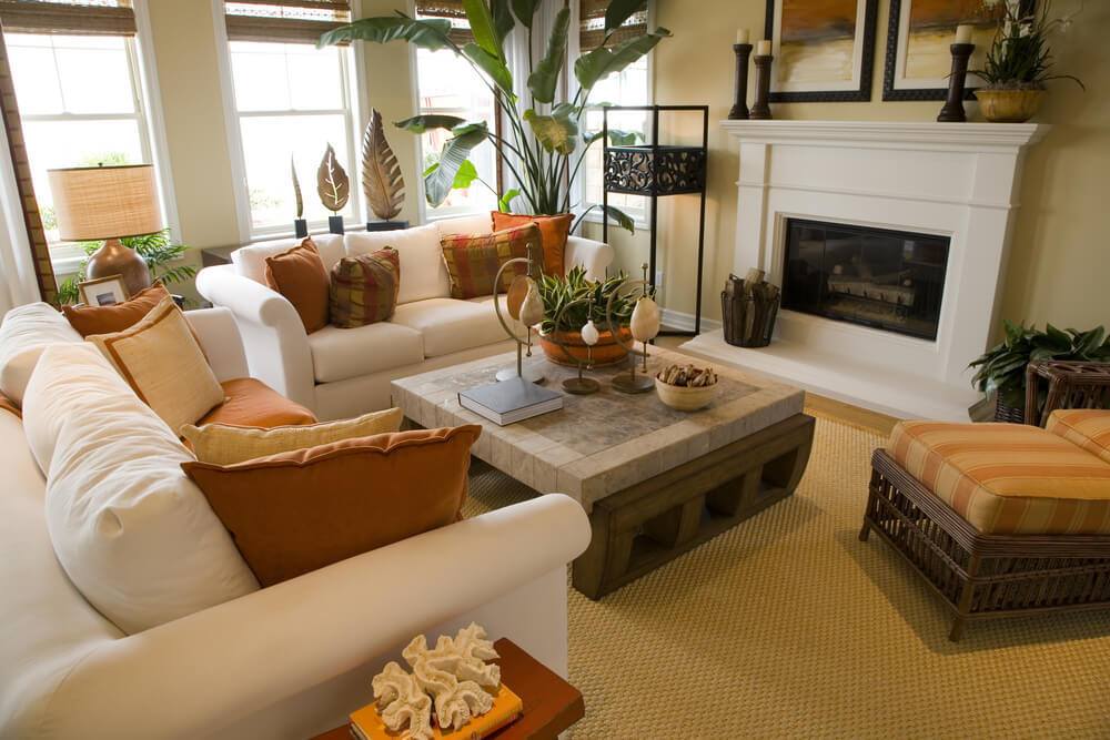 Bright and colorful living room design with off-white sofas decorated with  orange and brown