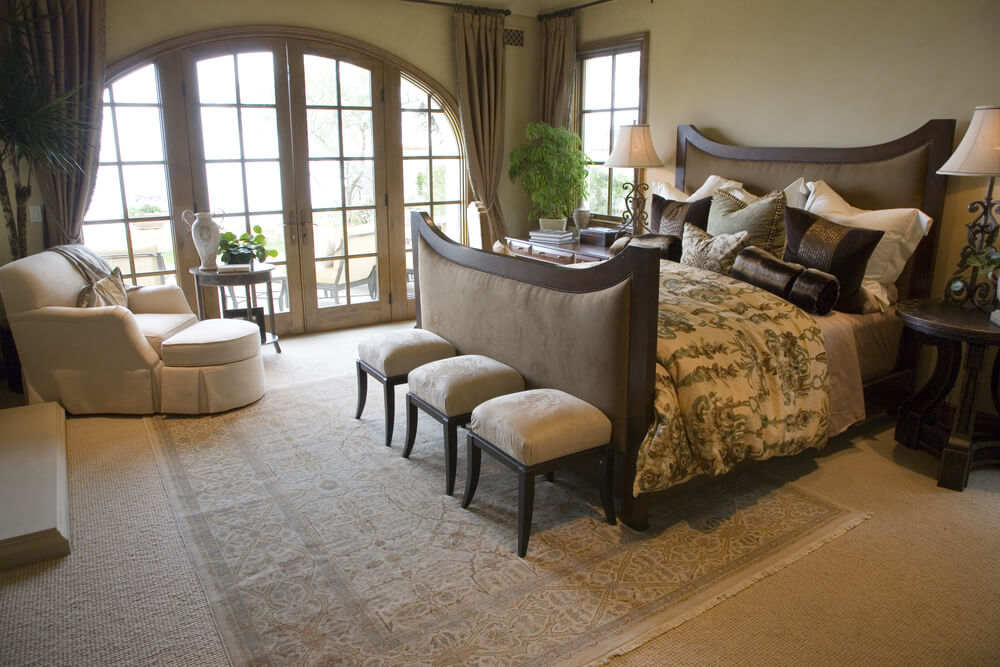 Open bedroom with a panoramic view through glass-paned French doors.