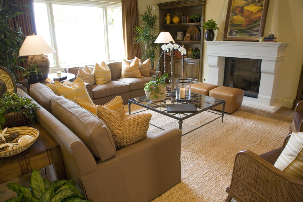 This living room is packed with seating, featuring two tan couches, leather ottomans, and two wicker and leather rocking chairs.
