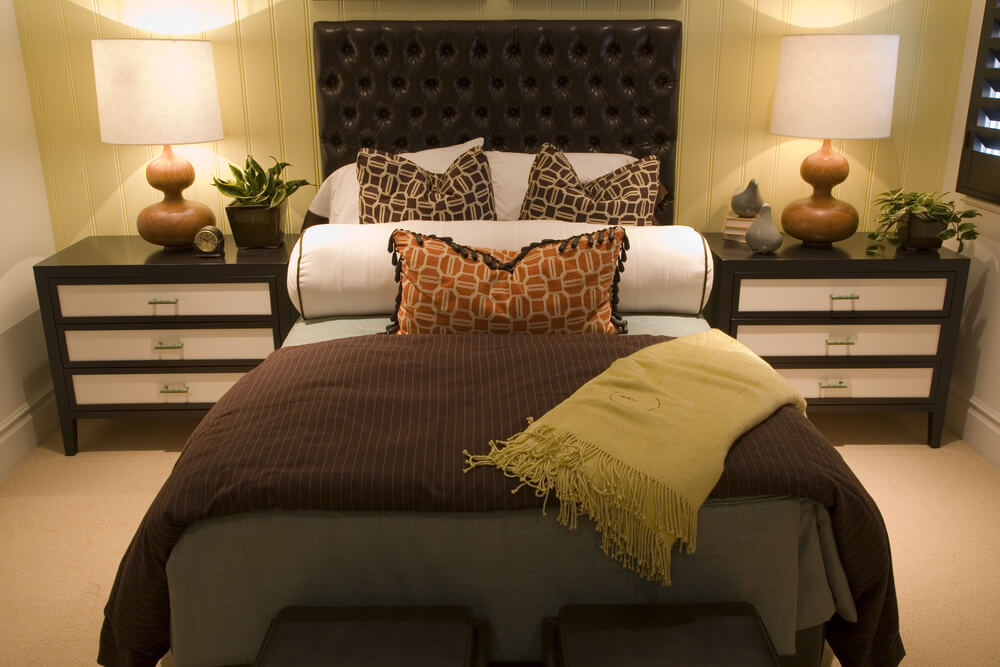 Tall dark leather headboard dominates this small bedroom  with white accents on dresser drawers and