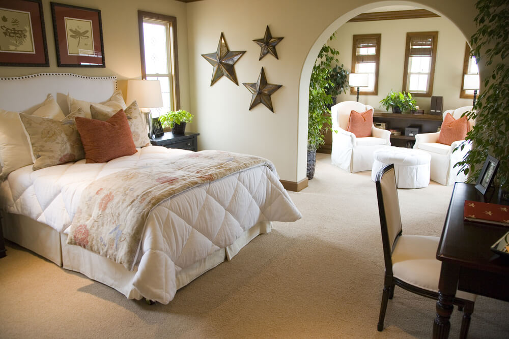 Bright Carpeted Master Bedroom With Arch Divide Copper Star Wall Accents White Bedding