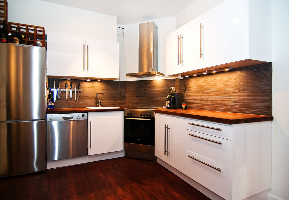 Small Kitchen Situated In Corner Of Room With White Cabinets And Dark Brown Back Splash