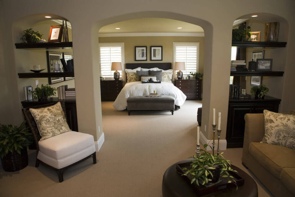 triple arches bisect this master bedroom segregating the sleeping and relaxing areas - Master Bedroom Interior Decorating
