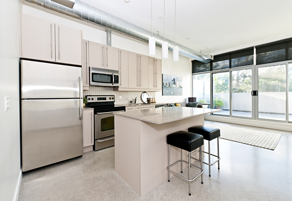 Small Kitchen With Stainless Steel Appliances Industrial Pipe Hanging From The Ceiling