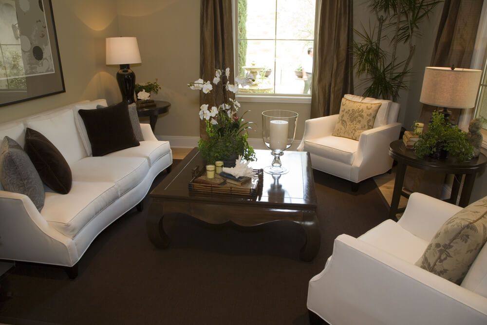 Centered around a polished square traditional coffee table, this living room features all-white chairs and sofa on a dark brown rug over hardwood flooring.