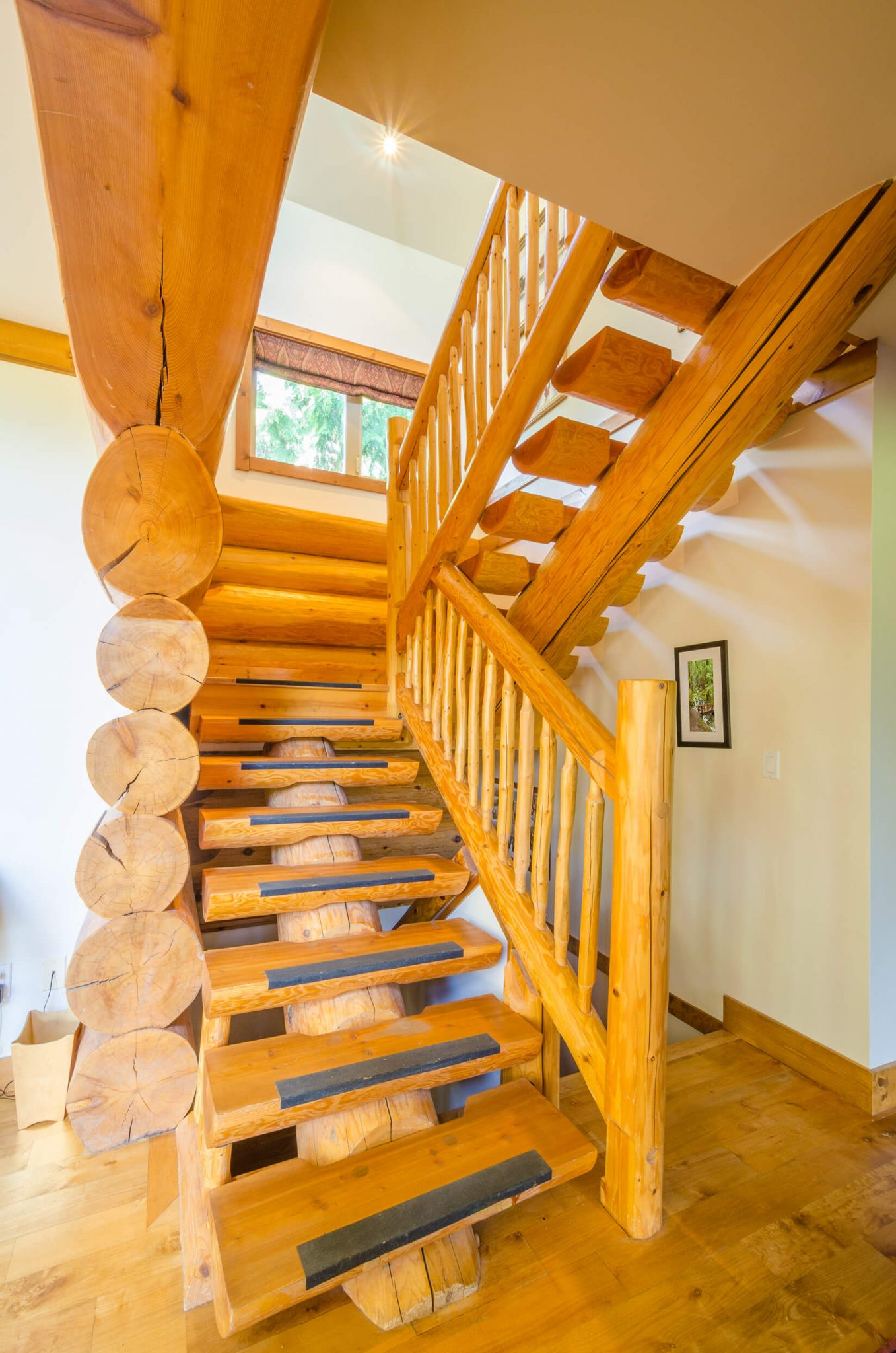 Log staircase with a single log stringer placing treads in groves. Baluster is also made of small logs.