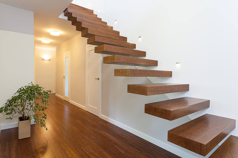 Modern staircase with floating treads jutting out of the wall.  No baluster or handrail.  Treads are entirely natural wood.