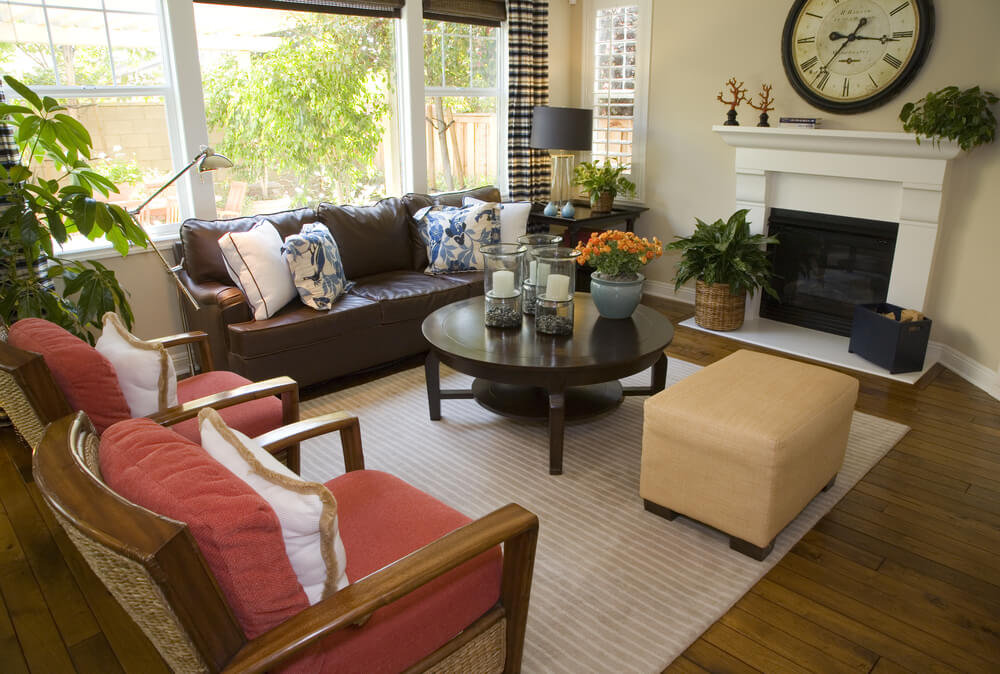 This living room features a variety of color, including red cushion armchairs, brown leather couch, and bright tan ottoman.