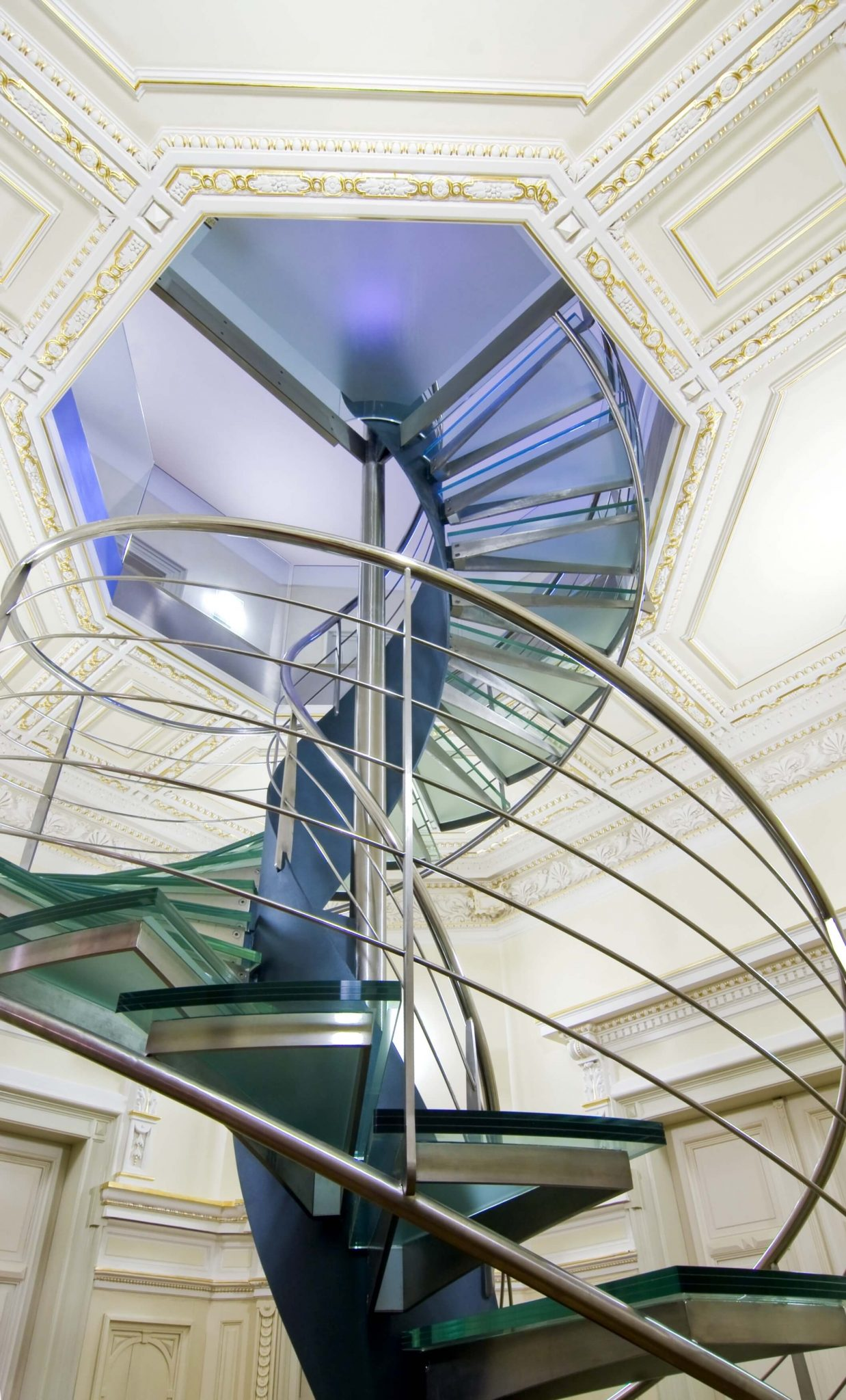 Spiral glass and steel staircase climbing to top of ornate dome room.