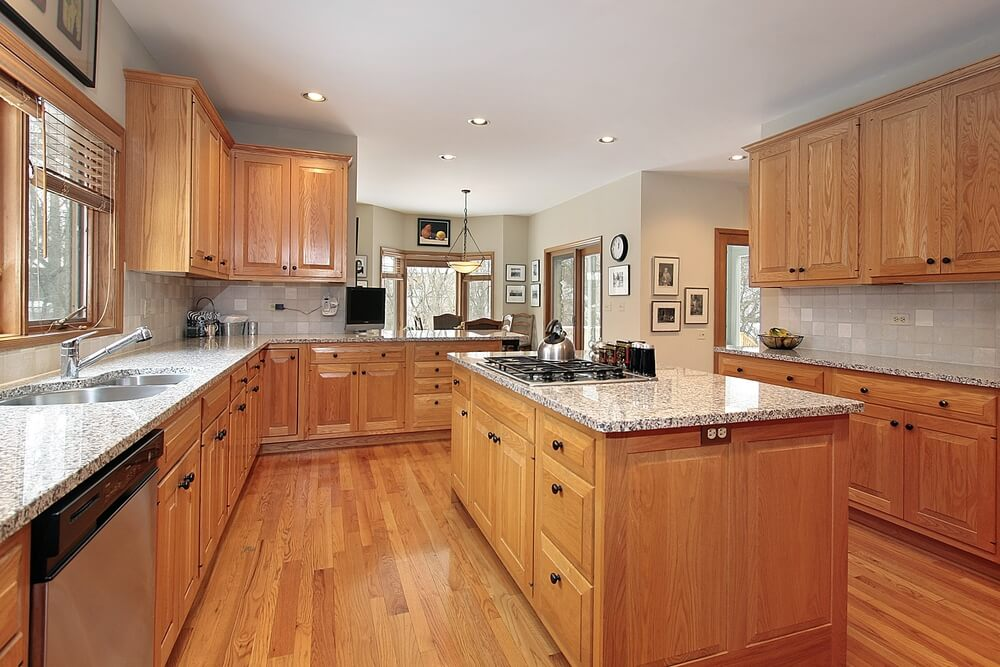This kitchen is awash in natural warm wood tones, punctuated with light granite countertops.