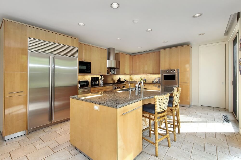 Example of a modern, minimalist kitchen using smooth natural wood surfaces, white tile flooring and ceiling, and brushed aluminum appliances.