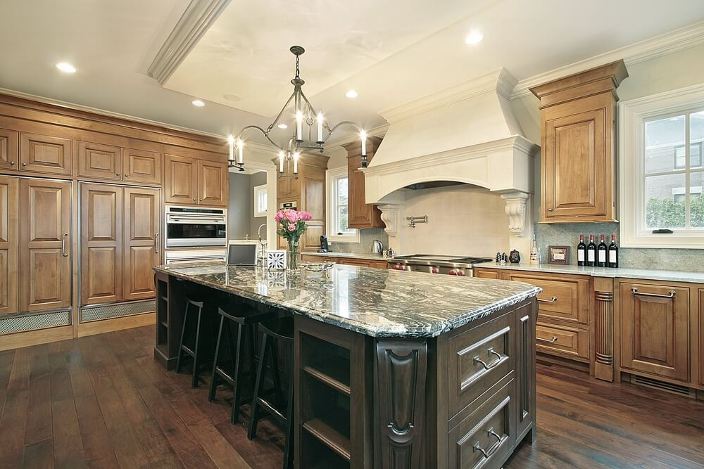 Dark Wooden Island With Marble Top Stands Out In This Kitchen Featuring Lighter Cabinets And