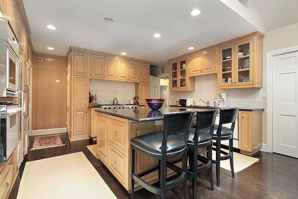 soft archways lead into this spacious kitchen with natural wood and