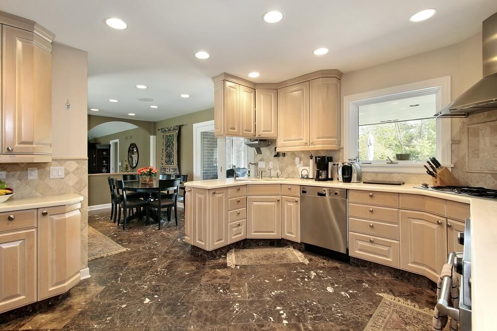 Rounded Kitchen Highlights Light Treated Wooden Cabinets With Recessed  Lighting Over Dark Tile Floor.