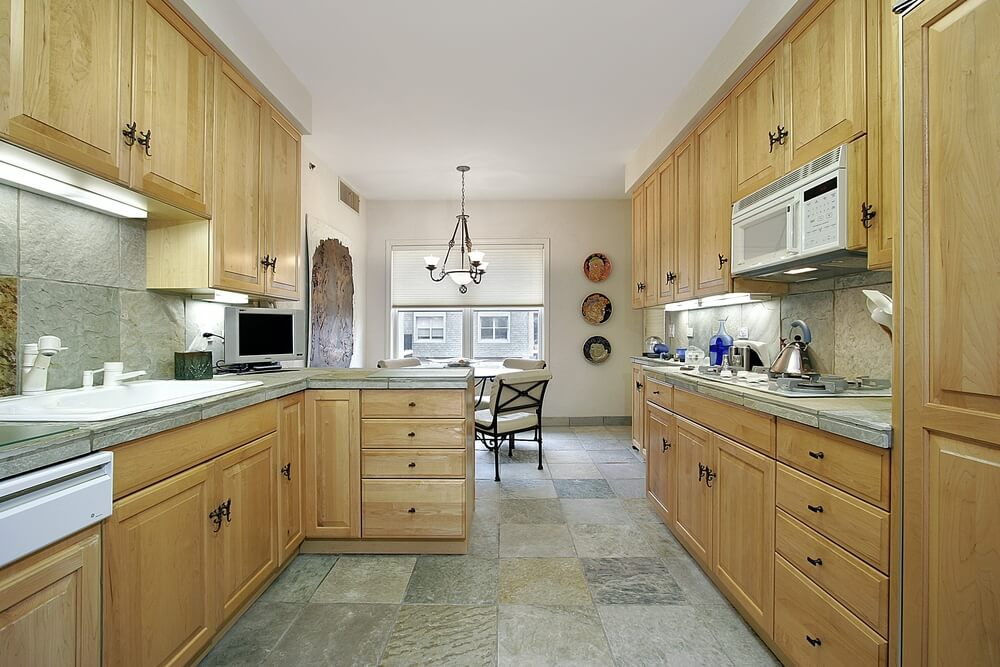 Long kitchen highlighted by natural light wood cabinets and drawers, along with matching stone backsplash and flooring.