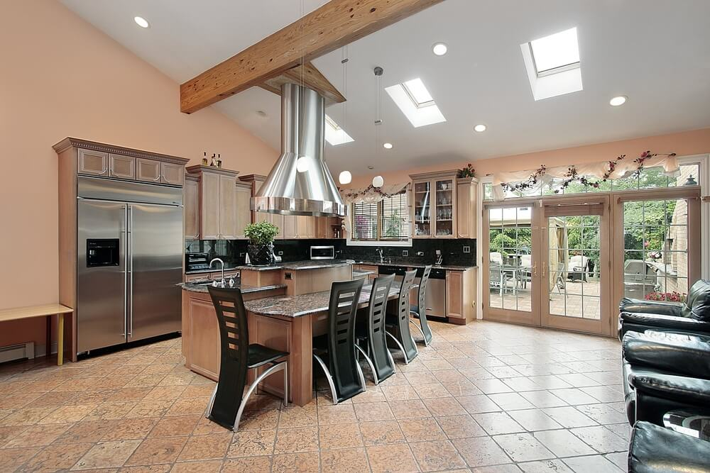 This kitchen features a bright mixture of modern and traditional looks, with exposed beams and cabinets in natural wood, while space age metal chairs and stove hood reflect the aluminum appliances.