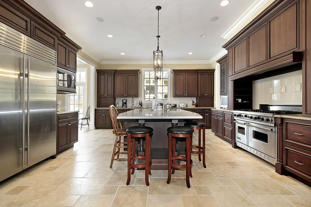 large custom kitchen with dark brown cabinets stainless steel appliances with extra large refrigerator