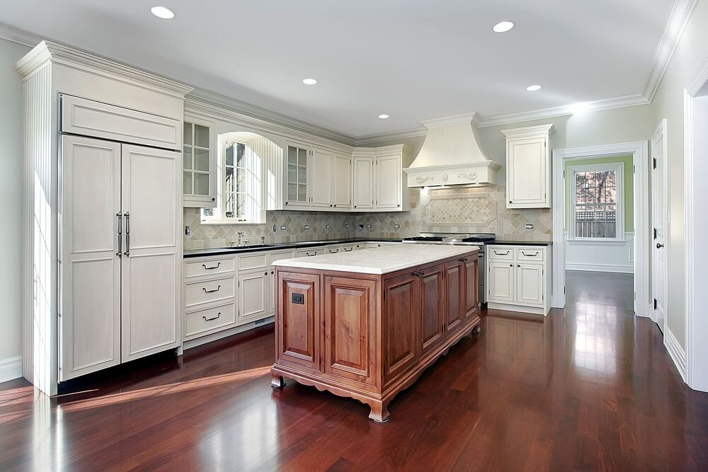 The white granite countertop on this minimalist island matches the cupboards, while the wood base itself reflects the warm tone of the flooring.
