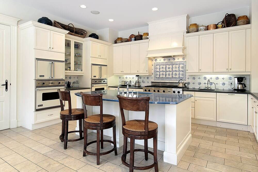 all white kitchen design featuring blue accents on backsplash and island countertop