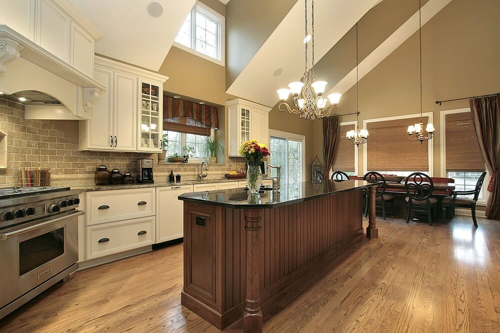 This kitchen displays a range of colors, from the natural hardwood flooring, to the dark wood and black countertop island, to the light brick backsplash and brushed aluminum appliances.