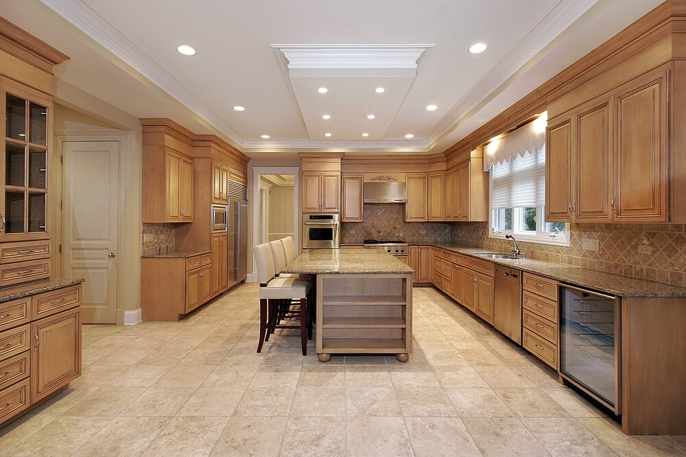 Massive Kitchen With Custom Natural Wood Cabinets Lining Three Walls With Long Island Running Down The