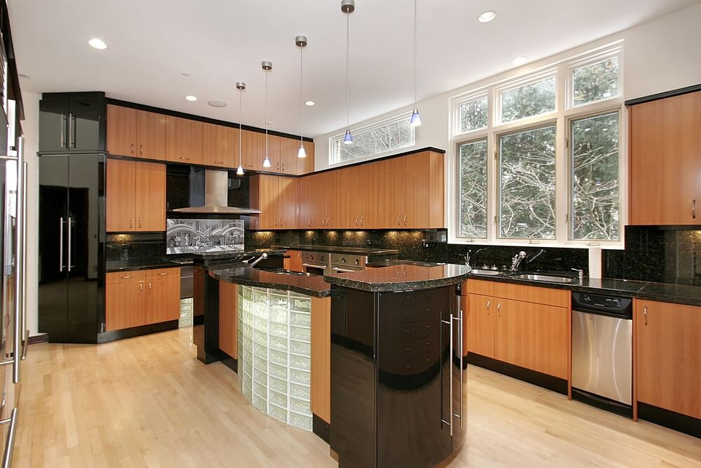Jet black backsplash and cupboards bisect the natural tones of the wooden cupboards in this modern kitchen.