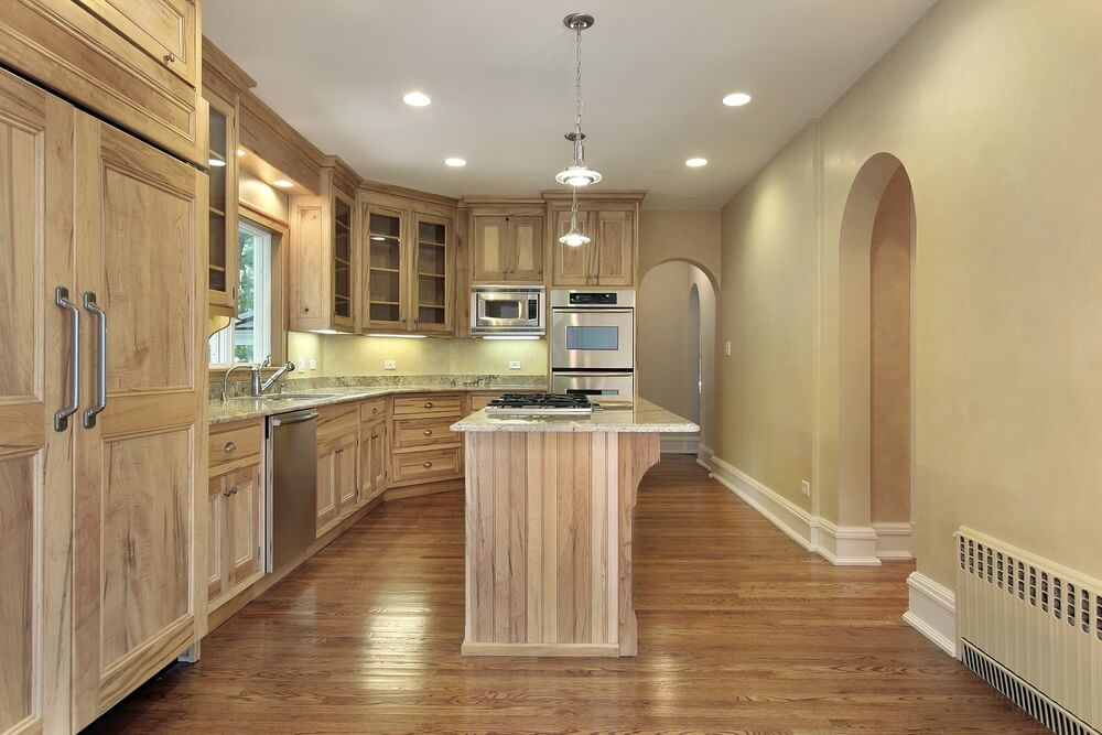 Soft archways lead into this spacious kitchen with natural wood and glass cupboards.