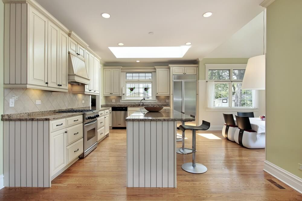 Elegant Large L Shaped White Kitchen With Island Opening Up To A Family Room. Large Part 21