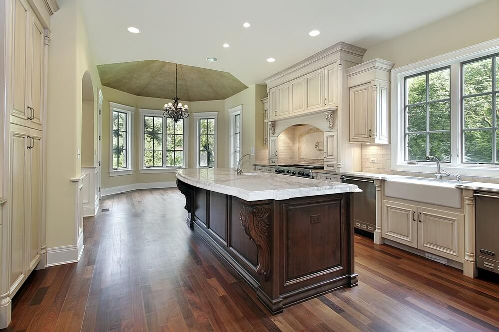 Large kitchen features a rotunda and dark hardwood flooring, with a massive granite countertop above the stained wood island.