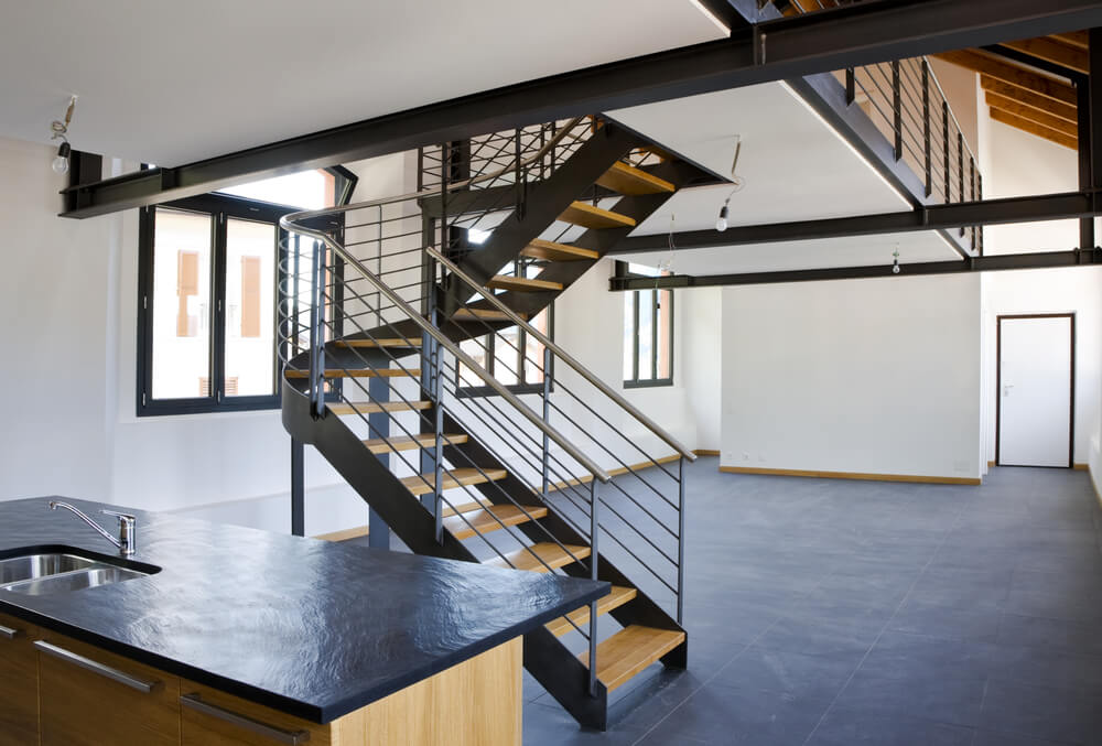 Half-landing steel and wood staircase leading up to loft space.