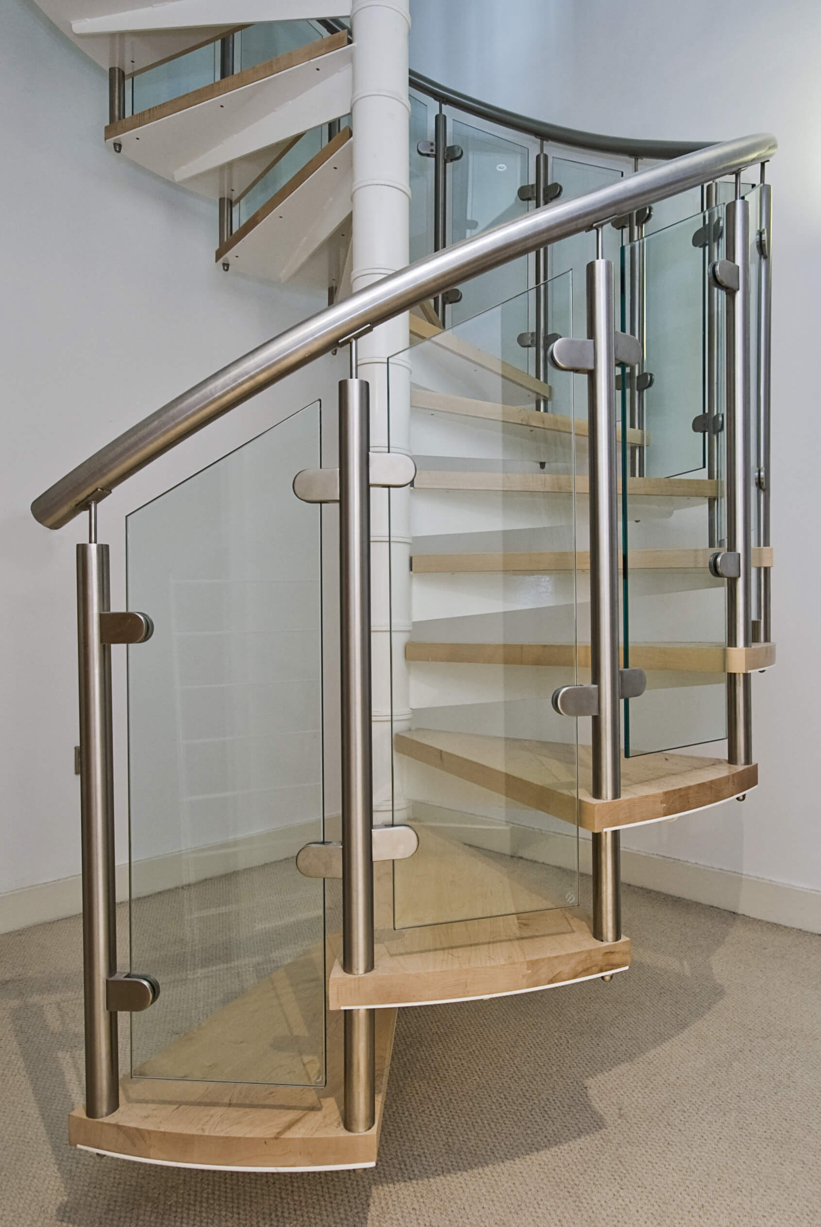 Close up of modern spiral staircase with wooden steps with open risers.  Glass and steel make up the baluster.
