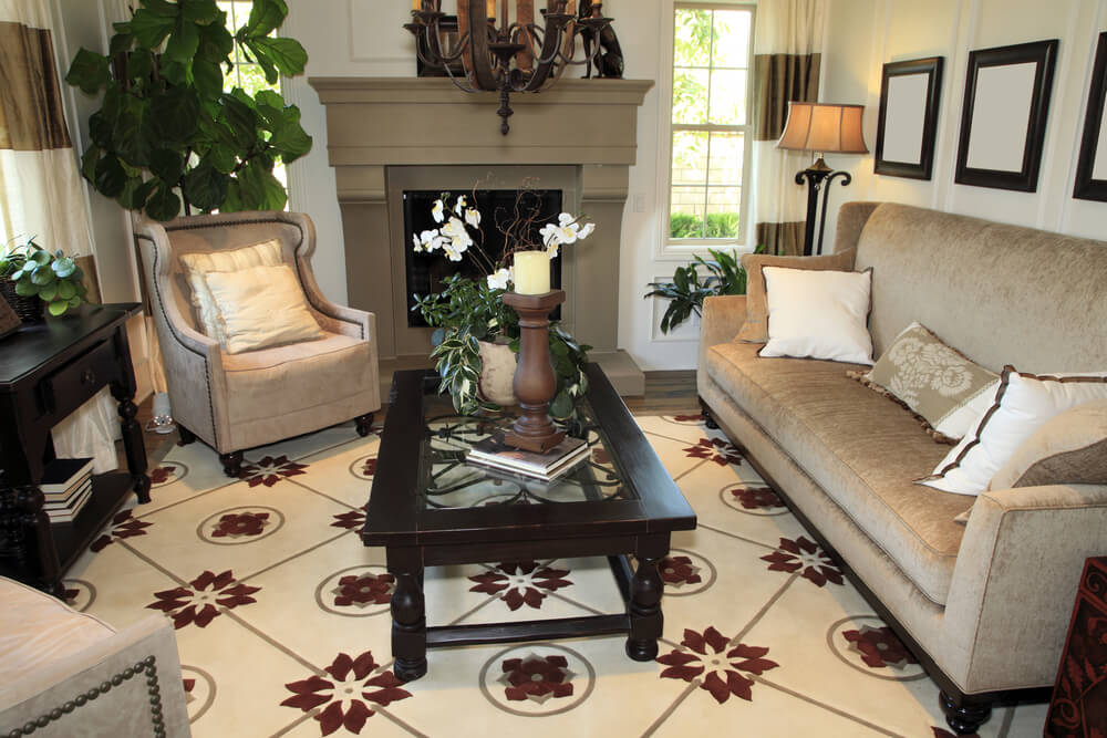 sandstone colored fireplace sits behind this living room centered around a glass surface coffee table