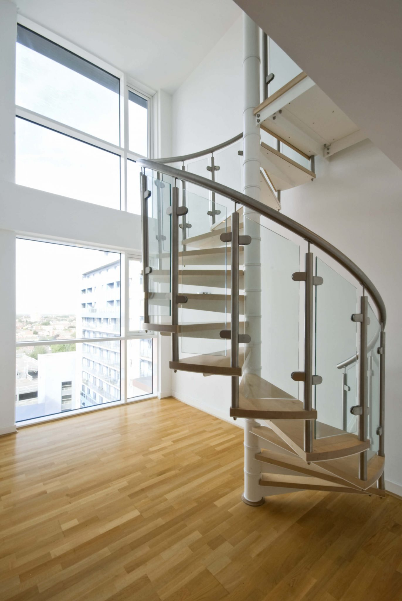 Spiral staircase with wood steps jutting from central white steel pole.  Baluster made up of steel handrail and glass.