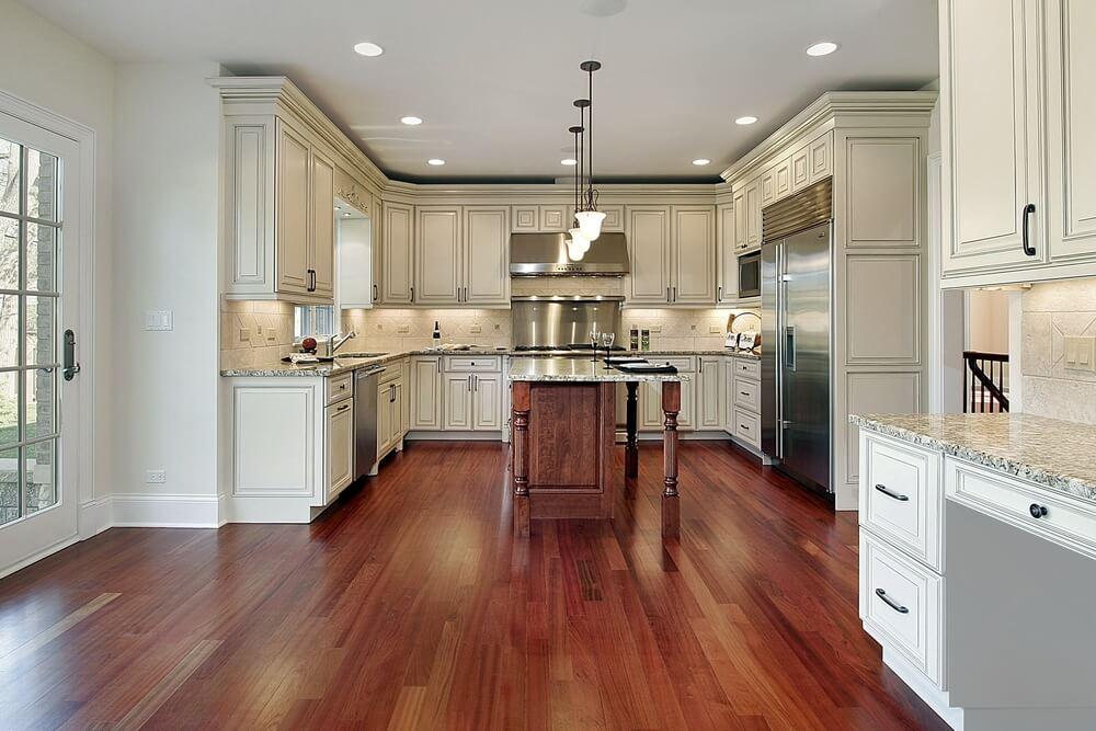 This kitchen features warm toned hardwood flooring and a matching island with light granite countertop all around.