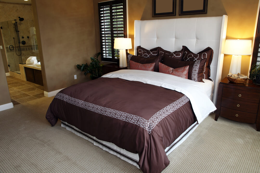 Adobe colors give a Southwest tint to this master bedroom featuring chestnut pillows and comforter on a pure white bed with matching large white headboard.